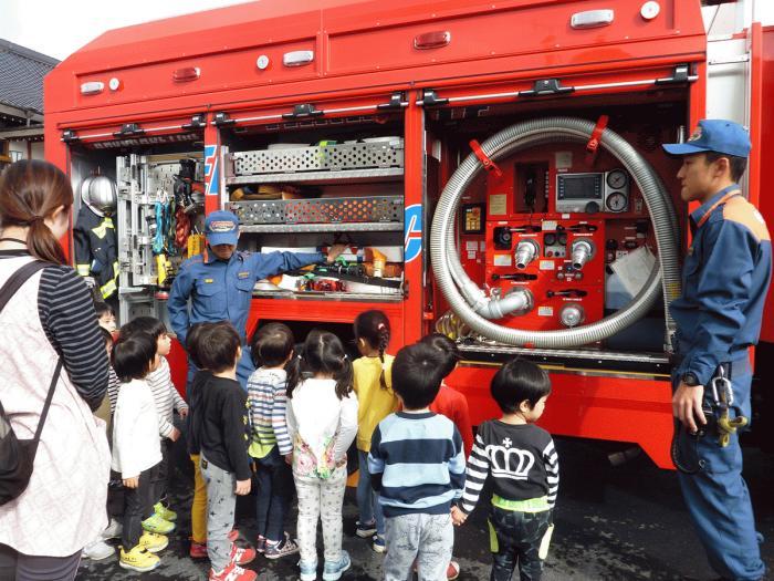 消防車の前で消防士の話を聞く園児達の様子